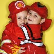 Twin boys dressed as firemen. - Stock Photo