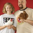 Smiling couple holding chickens. — Stock Photo