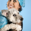 Smiling young woman holding dog. — Stock Photo