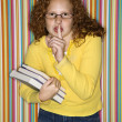 Girl holding books and shushing. - Stock Photo