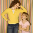 Girl leaning on smaller girl. - Stock Photo