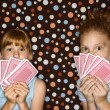 Girls holding playing cards. - Stock Photo