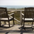 Постер, плакат: Chairs on Porch Facing Beach