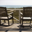 Chairs on Porch Facing Beach - Stock Photo
