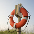 Stock Photo: Life preserver hanging on post.