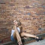 Woman against brick wall. — Stock Photo