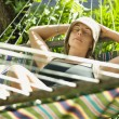 Woman relaxing in hammock. - Stock Photo