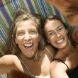 Women laughing in hammock. - Stock Photo