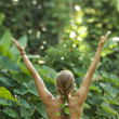 Nude woman with arms outstretched. - Stock Photo