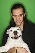 Man holding white dog on lap. — Stock Photo