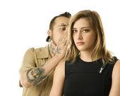 Tattooed man whispering to girl. — Stock Photo