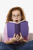Girl reading looking surprised. — Stock Photo