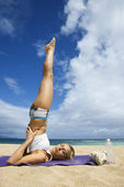 Woman doing yoga on beach. — Stock Photo