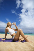 Attractive Young Woman Drinking on Beach — Stock Photo