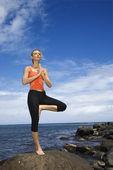 Woman doing yoga on rock. — Stock Photo