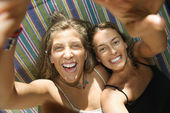 Women laughing in hammock. — Stock Photo