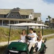 Family riding in golf cart. - Stock Photo