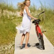 Girl Walking Bike on Boardwalk. - 图库照片