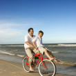 Dad riding red bicycle with son on handlebars. — Stock Photo