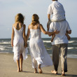 Family walking down beach. - Stock Photo