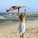 Girl holding kite on beach. — Stock Photo #9498121