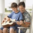 Father and Son Playing Guitar - Stock Photo
