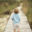 Little boy on beach walkway. - Stock Photo
