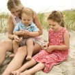 Mother and children looking at shells. — Stock Photo