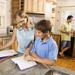Family in kitchen doing homework and chatting. - Stock Photo