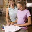 Mom helping daughter with homework. - Stockfoto