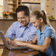 Man and Girl Working on Laptop - Stock Photo