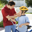 Dad helping son with helmet. — Stock Photo