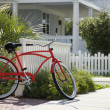 Red bicycle in front of house. — Stock Photo