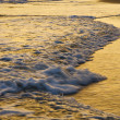 Stock Photo: Waves lapping beach at sunset.