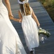 bride and flower girl on boardwalk — Stock Photo