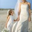 Bride and Flower Girl on Beach — Stock Photo