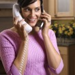 Woman Talking on Two Telephones - Stock Photo