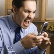 Man screaming into phone. - Stockfoto