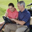 Couple in golf cart. — Stock Photo