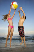 Boy and girl playing on beach. — Stock Photo