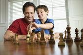 Dad teaching chess to son. — Stock Photo