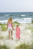 Sisters walking on beach. — Stock Photo