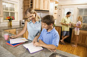 Family in kitchen doing homework and chatting. — 图库照片