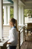 Girl standing on porch. — Stock Photo