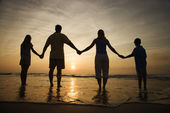 Family Holding Hands on Beach Watching the Sunset — Stock Photo