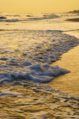 Waves lapping beach at sunset. — Stock Photo