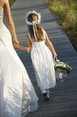 Bride and Flower Girl on Boardwalk — Stock Photo