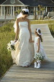 Bride and flower girl walking. — Стоковое фото