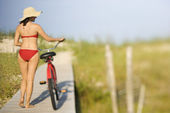 Donna con bicicletta in spiaggia — Foto Stock