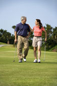 Couple walking on golf course — Stock fotografie